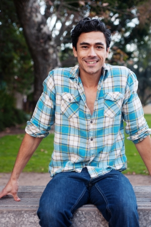 hispanic student: Happy young man sitting in a park smiling at the camera