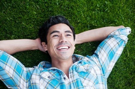 man looking at sky: happy young man lying in the grass looking up at the sky Stock Photo