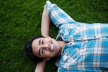 Glücklich junger Mann liegt im Gras suchen in den Himmel Standard-Bild - 13138120