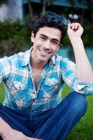 Gut aussehender junger Mann sitzt im Gras mit Sonnenbrille Standard-Bild - 13138106
