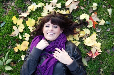 outsides: pretty young brunette girl lying in autumn leaves smiling Stock Photo