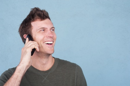portrait of a young handsome man on the cell phone outside isolated on a blue background photo