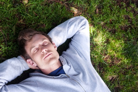 handsome young man sleeping in the grass in a park 版權商用圖片