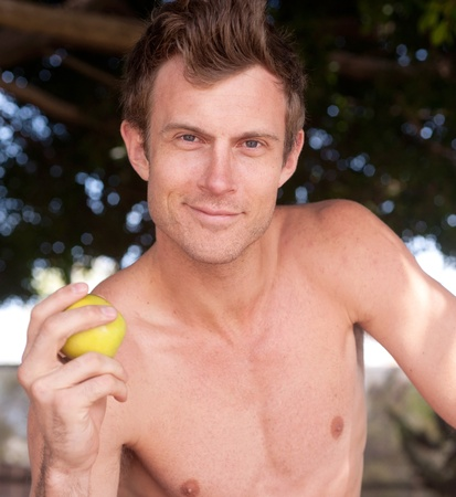 portrait of a young healthy shirtless man holding apple sitting outside photo