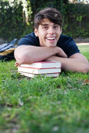 boy book: Young male student lying on grass with books in a park Stock Photo