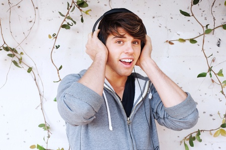 Young man with headphones listening to music against an ivy wall photo