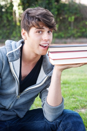 young male student on grass with books sitting in a park Stock Photo - 13138092