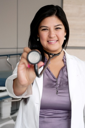 Portrait of young female doctor holding stethoscope photo