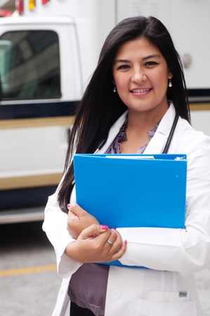 Portrait of young female doctor standing in front of an ambulance and holding a clipboard