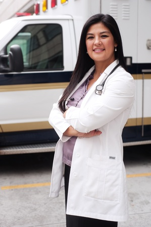 Portrait of young female doctor standing in front of an ambulance photo