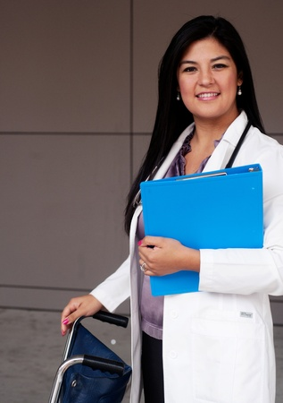 Portrait of young female doctor standing with wheelchair and holding a clipboard photo