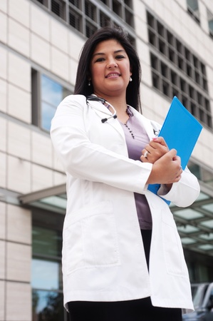 hospital staff: portrait of a young female doctor standing outside in front of a medical building holding a clipboard