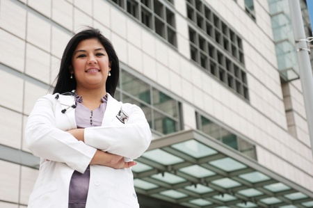 portrait of a young female doctor standing outside in front of a medical building photo