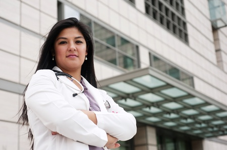 portrait of a young female doctor standing outside in front of a medical building