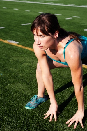 Female athlete stretching on an athletic field Stock Photo