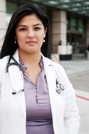 hospital staff: portrait of a young female doctor standing outside in front of a medical building