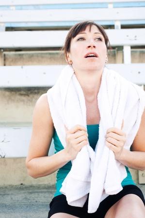 Müde weiblichen Athleten mit Handtuch sitzt auf der Tribüne Standard-Bild - 13139280