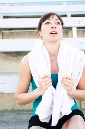 bleachers: Tired female athlete with towel sitting in the bleachers Stock Photo