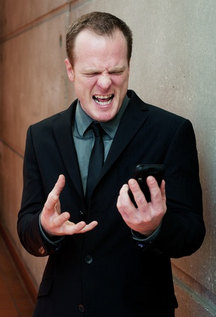 angry businessman, yelling at cell phone standing inside a building Stock Photo - 13138574