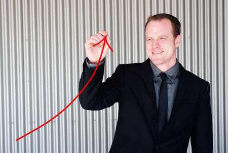 Professional businessman drawing a growth curve standing outside photo