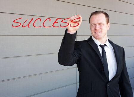 businessman writing the word success on screen standing outside photo
