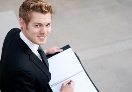 Portrait eines glücklichen jungen Geschäftsmann mit Notizbuch draußen sitzen Standard-Bild - 13139250