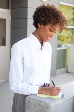 pretty African American executive standing outside with pen and paper Stock Photo - 13138626