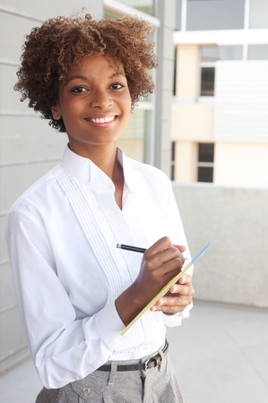 pretty African American executive standing outside with pen and paper Stock Photo - 13138689