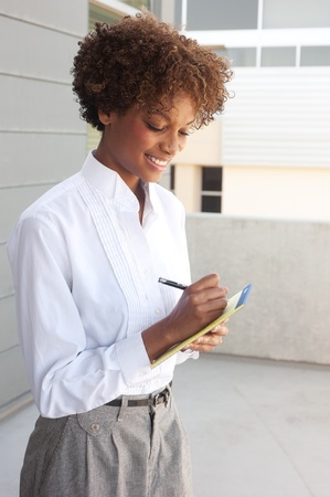 pretty African American executive standing outside with pen and paper Stock Photo - 13138625