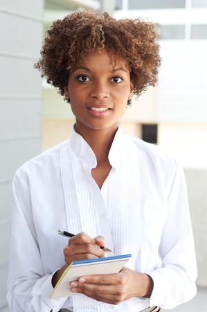 pretty African American executive standing outside with pen and paper photo