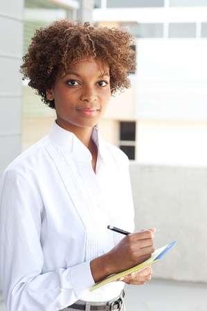 business focus: pretty African American executive standing outside with pen and paper