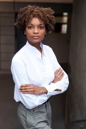 pretty African American executive standing outside with arms folded