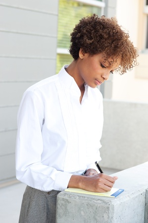 pretty African American executive standing outside with pen and paper Stock Photo - 13139254