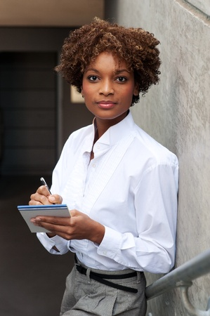 pretty African American executive sitting outside with pen and paper Stock Photo - 13138302
