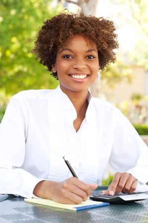 pretty African American executive sitting outside with pen and paper