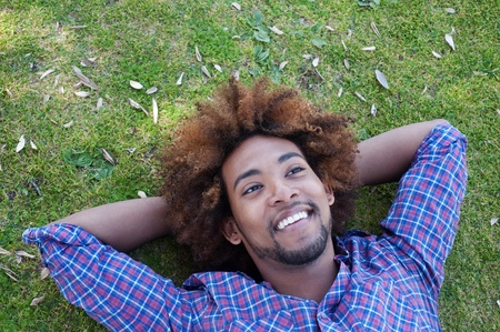 resting: young, happy african american male lying in grass
