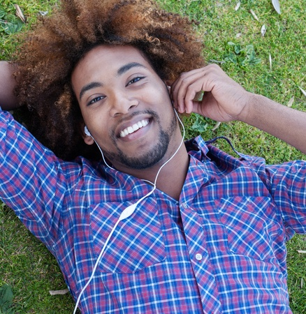 earphone: young, happy african american male lying in grass listening to music
