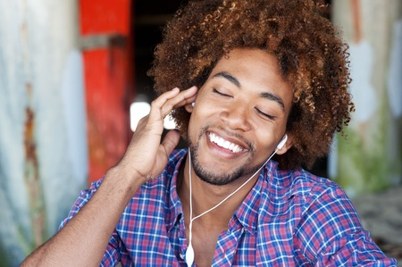 closeup portrait of a handsome African American man at the beach listening to music Standard-Bild