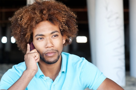 portrait of a young handsome African American on the phone at the beach
