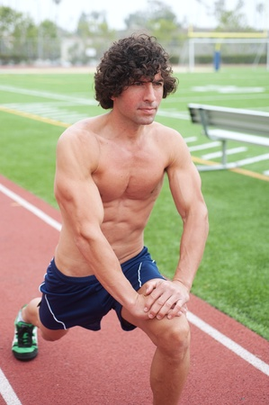 athletic male runner stretching on an athletic field photo