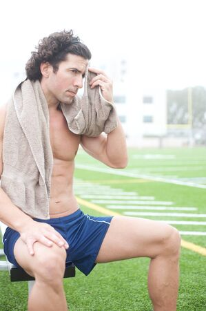 tired athletic male runner sitting in a stadium photo