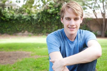 jonge mannelijke student zit in het gras en glimlachen