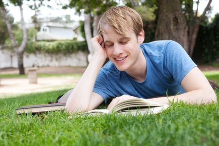 Young male student lying on grass with books Stock Photo - 13445786