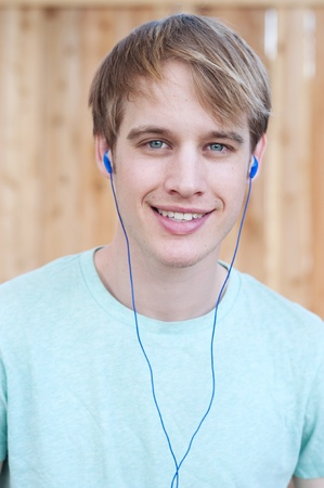 earphone: closeup of young male listening to music outside