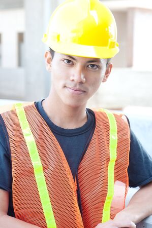 portrait of a young asian construction worker standing outside Banco de Imagens