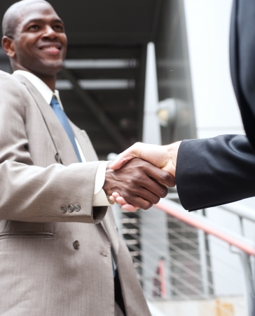 closeup of African American businessman shaking hands with caucasian businessman photo