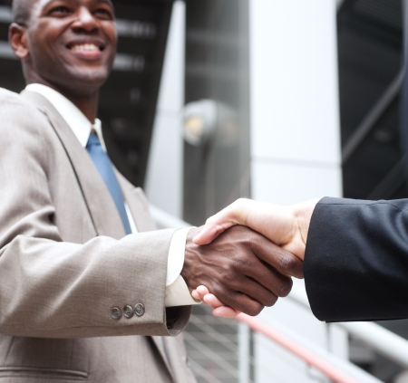 trust people: closeup of African American businessman shaking hands with caucasian businessman