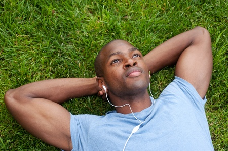 portrait of an African American man lying in grass listening to music photo