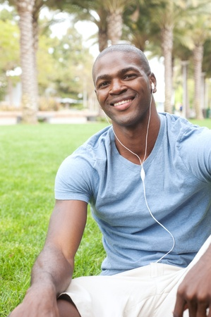 sexy headphones: portrait of an African American male student sitting in grass on campus Stock Photo