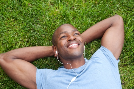 earphone: portrait of an African American man lying in grass listening to music Stock Photo